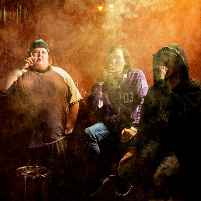 Viisi nuorta miestä polttavat tupakkaa baarin tupakkakopissa.