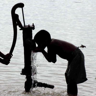 Intialaiset lapset juovat vettä pumppukaivosta.