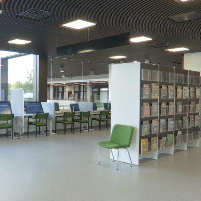 Tyhjä kirjaston lehtisali. Seinustalla asiakkaiden käytössä olevia tietokoneita.