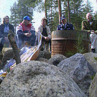 """Jyväskylän Tikkakosken """"Puuhamaassa"""" kunnan työntekijät, paikallispoliisi ja päihdeongelmaisten edustaja istuvat penkillä."""