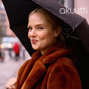 Artisti Titta Hakala seisoo kadulla mustan sateenvarjon alla. Taka-alalla hämyisenä näkyy lastenhoitajia vaunujen ja kädestä pitävien lasten kanssa.