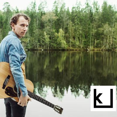Kirjailija Juha Itkonen kitaran kanssa rannalla