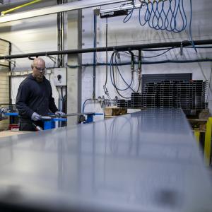 Mies valmistelee metallikappaleita hitsausrobotin käsittelyä varten.