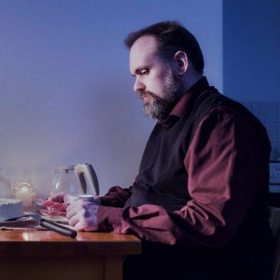 Sauli Paavola sitter ensam vid ett bord dukat för två.