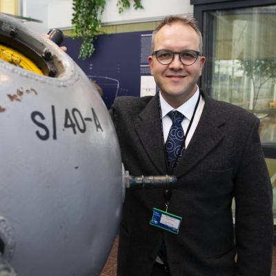 Mies hymyilee ja nojaa pallonmuotoiseen merimiinaan näyttelyssä.