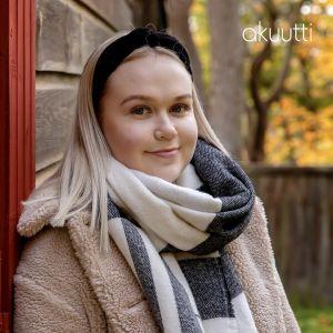Hymyilevä nainen nojaa talon seinään, katsoo kameraan.