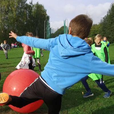 Lågstadiebarn spelar fotboll med gymnastikboll