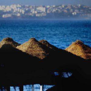 Auringonlasku rantavarjoihin, taustalla meri ja kaupunkia.