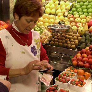 Mies hedelmäostoksilla kauppahallissa, myyjää laskee hintaa.