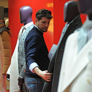 Miesten pukuihin puettuja mallinukkeja sekä mies, joka katselee vaatteita.