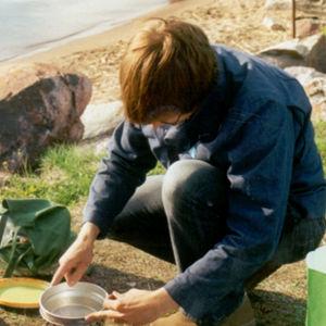 Mies keittää vettä retkikeittimellä.