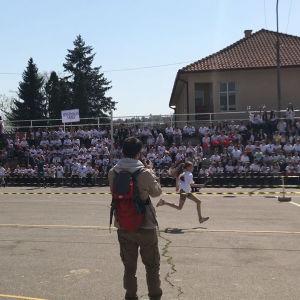 Två unga kvinnor springer över en asfaltplan. I bakgrunden hejar barn på en läktare. En man i framgrunden fotograferar.
