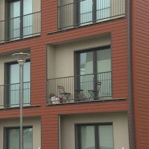 En röd höghusfasad i trä, balkonger med balkongmöbler i.