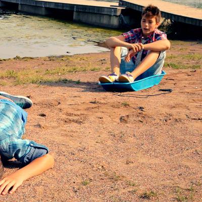 Pojke liggar i sanden. En annan sitter i en pulka.