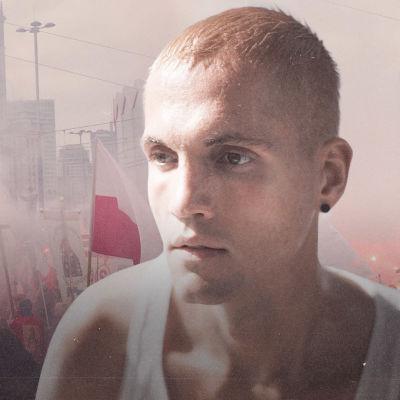 Muotokuva vaaleahiuksisesta nuorehkosta miehestä. Taustalla kulkue, jossa ihmiset kantavat soihtuja ja ristejä.