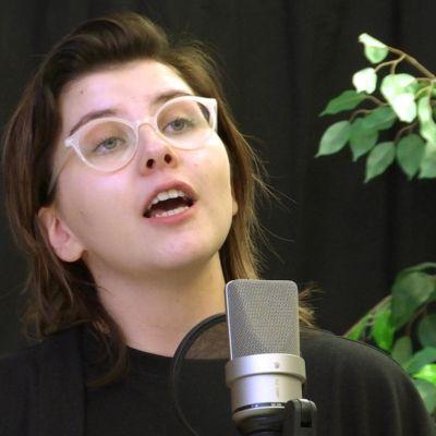 En ung kvinna med glasögon står vid en microfon och rappar.