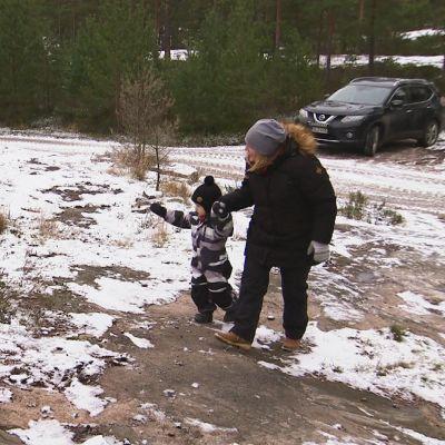 Ett barn pekar mot en röd tomteluva på marken.