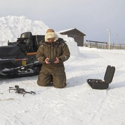 Poromies Vesa Länsman lennättää droonia.