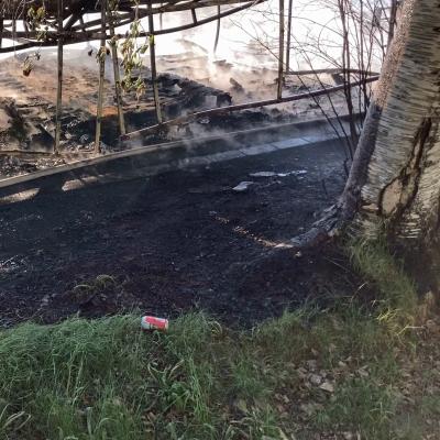 Palanut rakennelma savuaa Rovaniemen keskuskentällä ja viereisen koivun kylki on mustunut