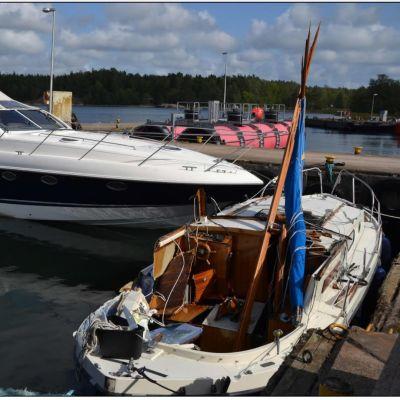 Två båtar förtöjda vid en brygga efter att de kolliderat med varandra. Den mindre båten, en motorseglare, har stora skador på babords sida.