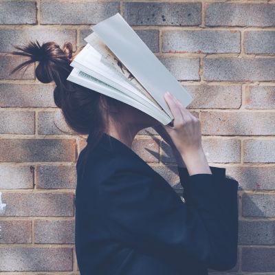 Nainen peittää kasvonsa kirjalla.