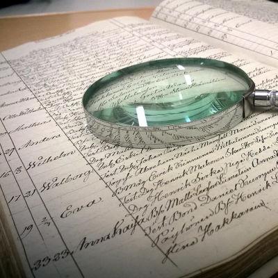 En öppen bok ligger på ett bord med ett förstoringsglas på.