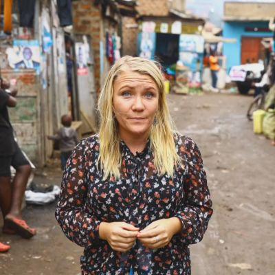 En blond kvinna står på en lerig gata i Uganda.
