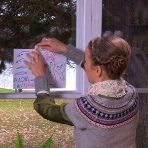 Tejpa teckningen på fönstret.