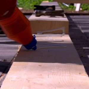 Plankorna till takstolsbalk limmas ihop.