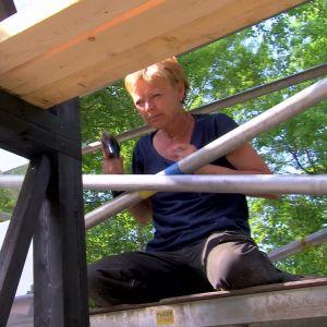 Susanna skruvar fast växthuset fönster direkt i väggstommen