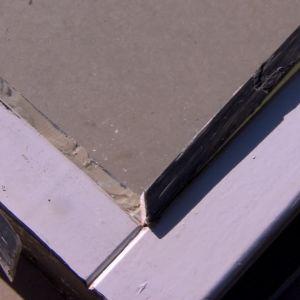 Det triangelformade glaset kittas fast i fönsterbågen