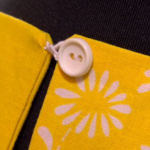 Klänningen fästs i ryggen med en söt knapp
