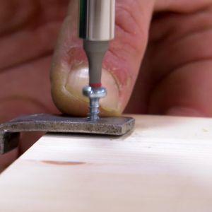 Jim skruvar fast metallvinkeln i hyllan