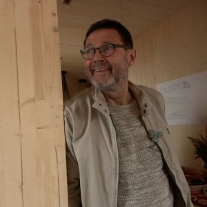 Mies hymyilee seinäelementin vieressä