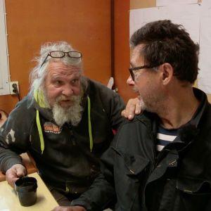 Kaksi miestä juttelevat rakennustyömaan kopissa