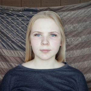 Kuva nuoresta naisesta Yhdysvaltain lipun edessä.