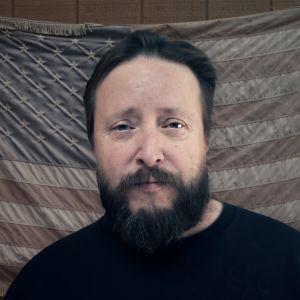Kuva miehestä Yhdysvaltain lipun edessä.