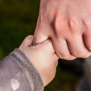 Lapsi ja äiti pitävät toisiaan kädestä.