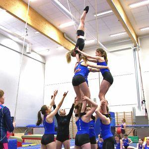 Gymnaster övar akrobatiskt element.