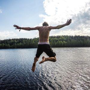 Mies hyppää veteen.