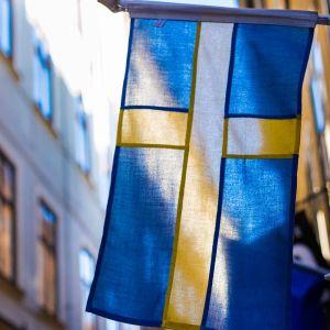 Ruotsin lippu, taustalla katunäkymää Tukholmasta.