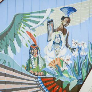Kirkasvärisiä maalauksia kirkon katossa, papukaija, eri etnisiä ryhmiä edustavia enkeleitä.