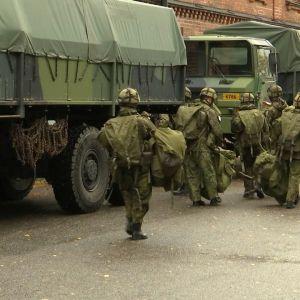militär med packning invid lastbilar