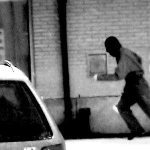 Naamiomies juoksee rakennuksen vieressä