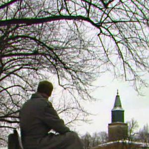 Mies istuu puistonpenkillä ja taustalla näkyy kirkko