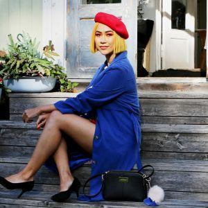Sini Laitinen istuu talon portailla. On kukkia ja kaunis kesäpäivä.