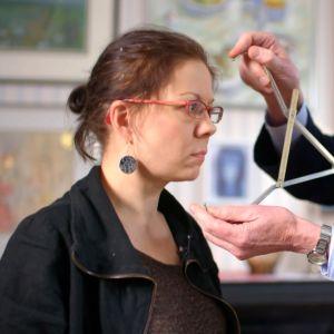Toimittaja Riikka Kaihovaaran kasvonpiirteitä mitataan kalloharpilla.
