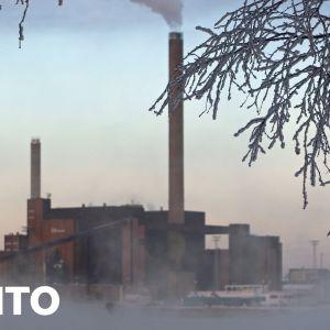 hiilivoimala, jonka piipusta tupruttaa savua talvimaisemassa.