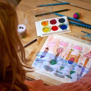 Lapsi piirtää vesiväreillä.