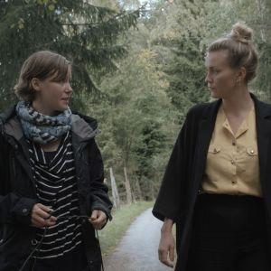 Maria Holmberg och Märta Westerlund promenerar på en skogsväg i Pargas.